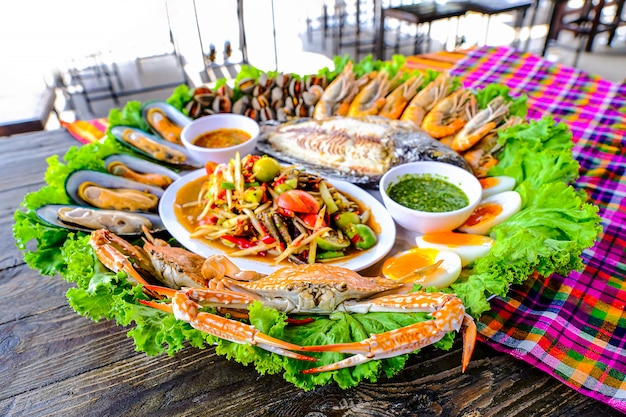 Seafood somtum tem mariscos, camarão, caranguejos, ovos cozidos, tilápia grelhada