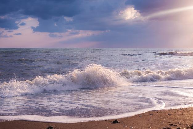 Seascape bonito com o barco no horizonte. céu nublado com raios dourados do sol, costa de areia