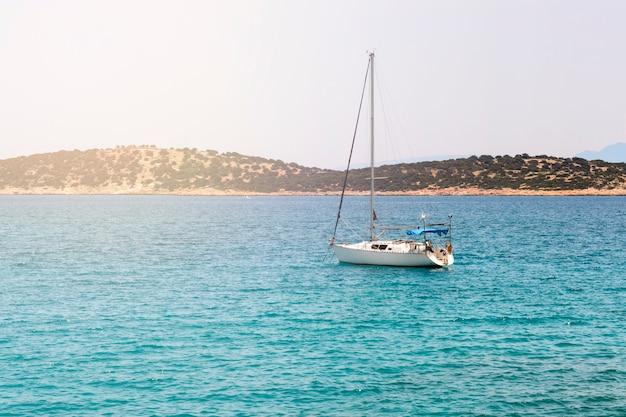 Seascape bonito com o iate branco da navigação no mar azul.