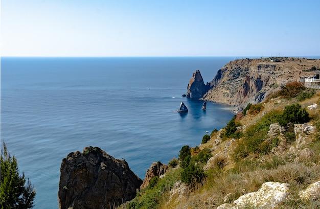 Seascape, céu, montanhas, mar, grandes pedras na costa.