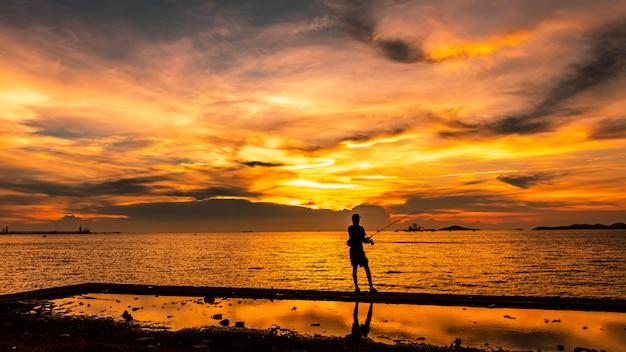 Seascape crepúsculo, a, pôr do sol, e, luz, ouro, com, pescador, silueta, primeiro plano