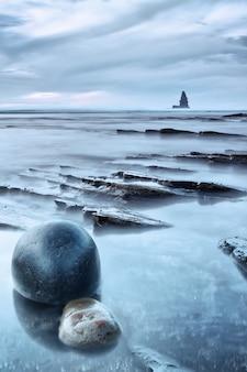 Seascape de rochas e mar ao pôr do sol. uma pedra redonda em primeiro plano.