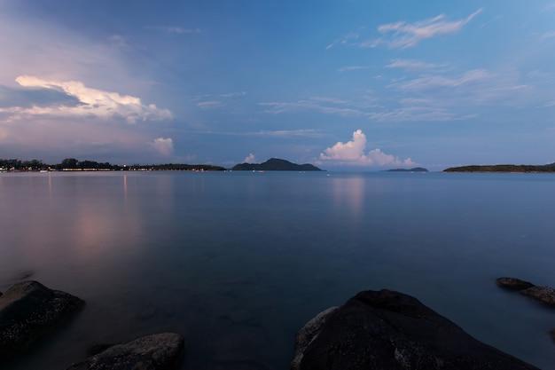 Seascape dramático do céu e da onda com a rocha no fundo do cenário do por do sol