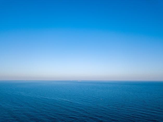 Seascape idílico com água azul e linha do horizonte manchada. vista aérea do zangão. fundo natural, lugar para texto.