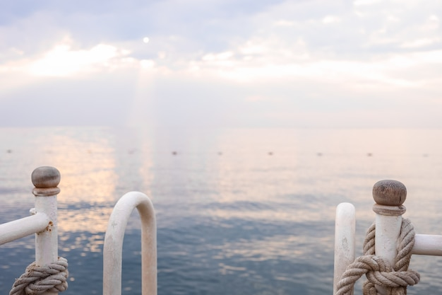Seascape no nascer do sol e trilhos de metal com cordas em primeiro plano