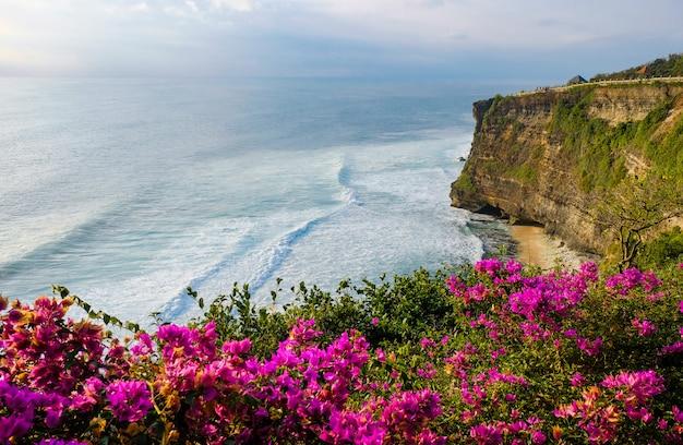 Seascape, oceano ao pôr do sol. as flores no oceano ajardinam o fundo perto do templo de uluwatu no por do sol, bali, indonésia.