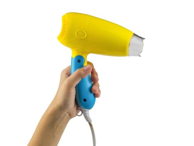 Secador de cabelo amarelo-azul na mão esquerda, isolado na superfície branca. acessórios para secar o cabelo.