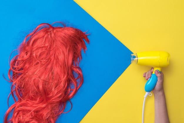 Secador de cabelo desenhado simulando o fluxo de ar na peruca laranja. conceito de cuidados com os cabelos. crie um novo estilo.