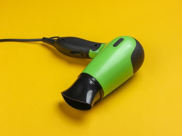 Secador de cabelo elegante em close-up de fundo amarelo de estúdio