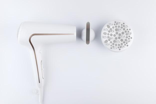 Secador de cabelo para secar cabelos com bocal difuso e plano para pentear sobre fundo branco. vista do topo.