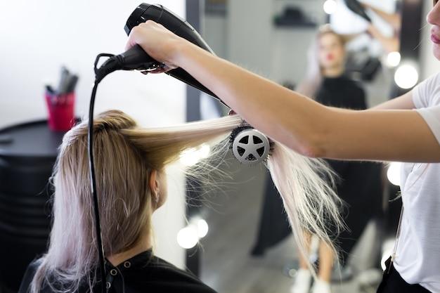 Secagem de cabelo loiro comprido com secador de cabelo e escova redonda