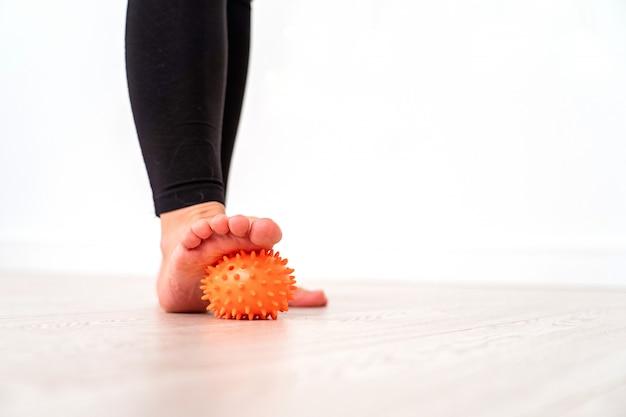 Seção baixa da menina que exercita com a bola do esforço no hospital. bola de massagem sob os pés.