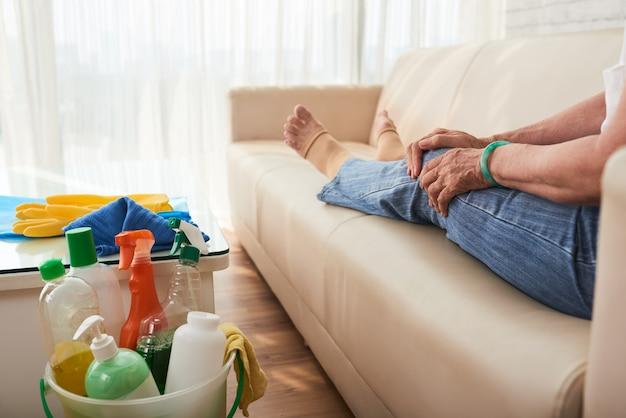 Seção baixa da mulher irreconhecível cortada, descansando no sofá após a limpeza da casa
