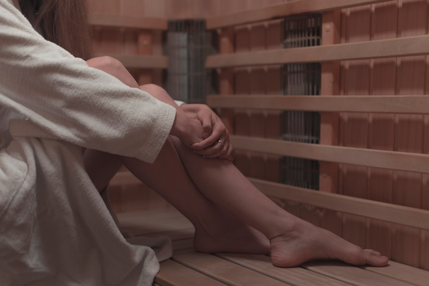 Seção baixa da mulher sentada no banco de madeira na sauna