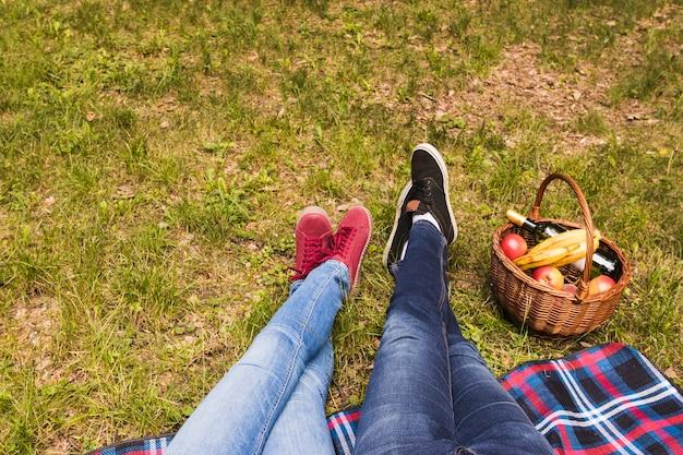 Seção baixa da perna do casal na grama verde com cesta de piquenique