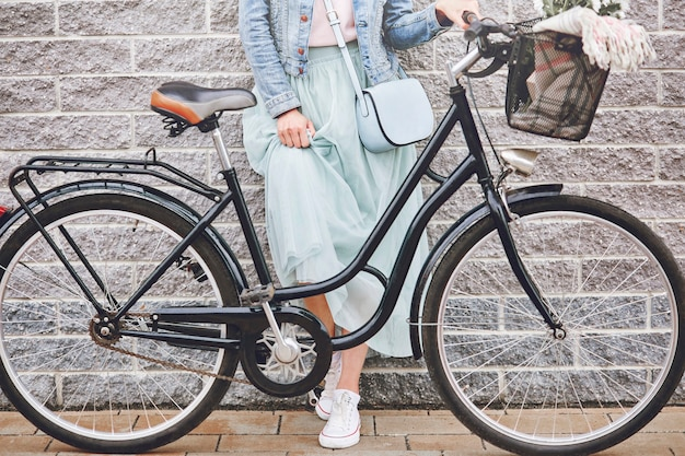Seção baixa das pernas femininas com bicicleta