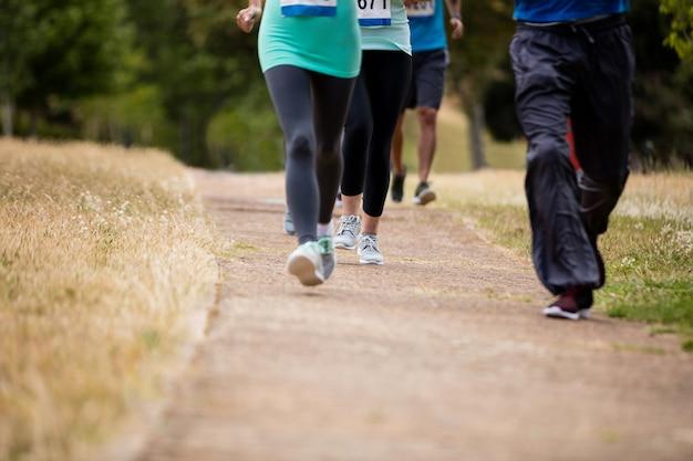 Seção baixa de atletas correndo corrida no parque