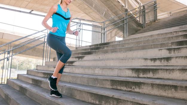 Seção baixa, de, condicão física, mulher jovem, sacudindo, ligado, escadaria