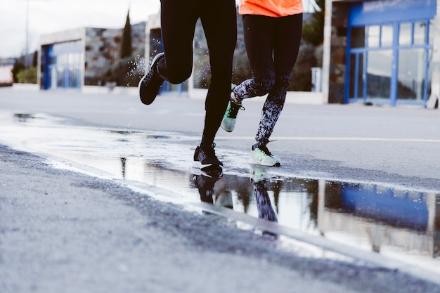 Seção baixa de dois atletas correndo na rua