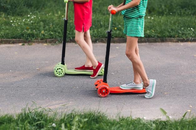 Seção baixa, de, duas meninas, montando, pontapé scooter, parque