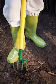 Seção baixa de jardineiro com garfo de jardinagem na fazenda