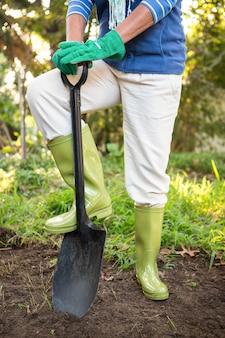 Seção baixa de jardineiro em pé com pá no jardim