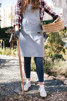 Seção baixa, de, jardineiro fêmea, com, cesta, e, enxada, em, mãos