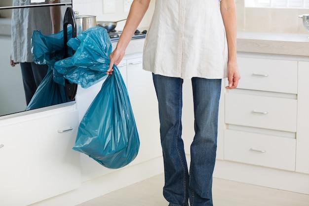 Seção baixa, de, mulher, carregar, bolsa lixo, em, cozinha