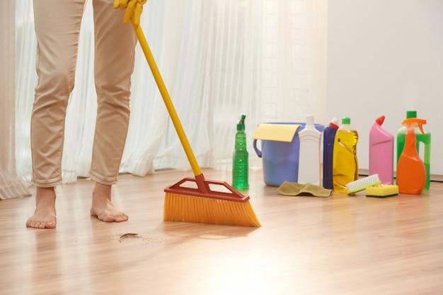 Seção baixa de mulher irreconhecível, varrendo o chão com vassoura