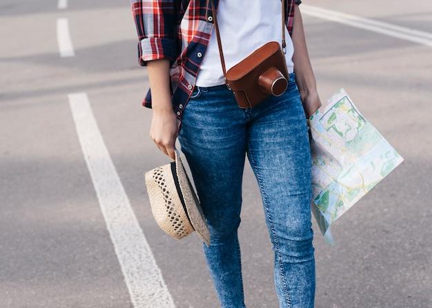 Seção baixa, de, mulher, viajante, segurando, mapa, e, chapéu, enquanto, andar, ligado, rua