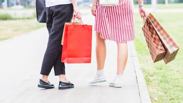 Seção baixa, de, mulheres jovens, segurando, bolsas para compras