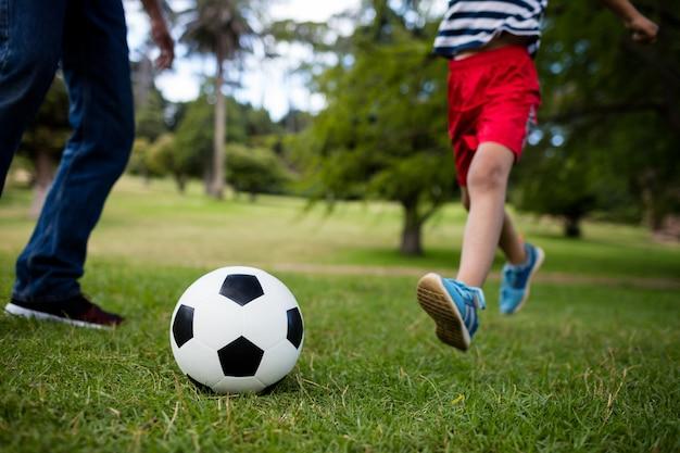 Seção baixa de pai e filho jogando futebol