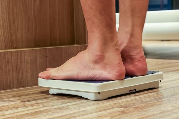 Seção baixa de pessoas em pé na escala de pesagem