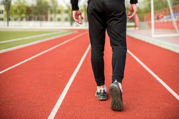 Seção baixa de um atleta do sexo masculino andando na pista de corrida vermelha