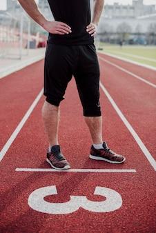 Seção baixa de um atleta na linha de partida da pista de corrida com o número três