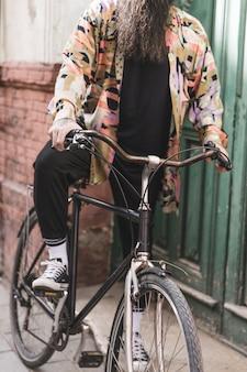 Seção baixa de um homem andando de bicicleta ao ar livre