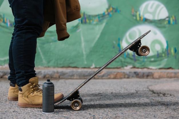 Seção baixa, de, um, homem, com, skateboard, e, lata aerossol