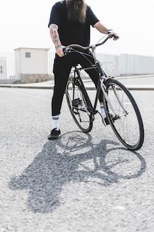 Seção baixa de um homem sentado na bicicleta