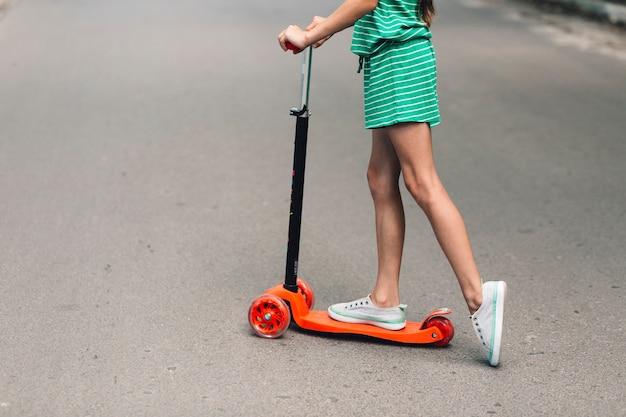 Seção baixa, de, um, menina, montando, empurre scooter, ligado, rua