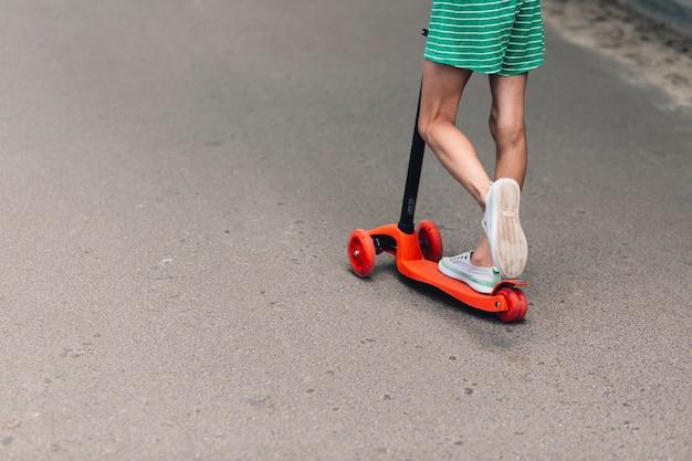 Seção baixa, de, um, menina, montando, scooter, ligado, estrada