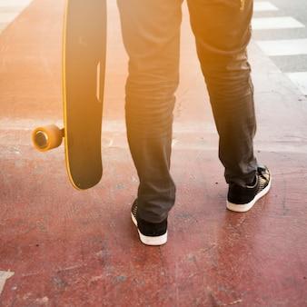 Seção baixa, de, um, pessoa, segurando, skateboard