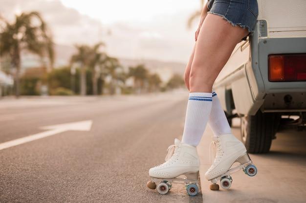 Seção baixa de uma mulher usando patins inclinando-se perto da van na estrada