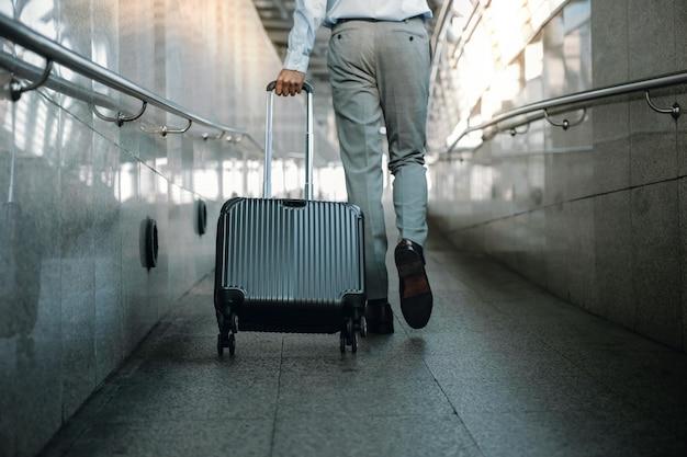 Seção baixa do empresário de passageiros andando com a mala na passarela no aeroporto.