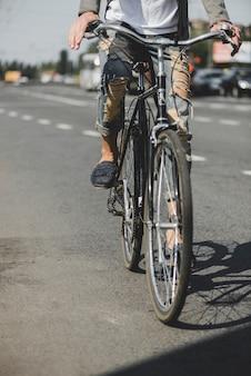 Seção baixa do homem andando de bicicleta na estrada