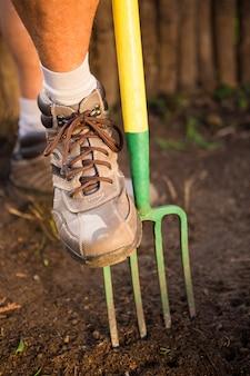Seção baixa do jardineiro masculino pisando no garfo no jardim