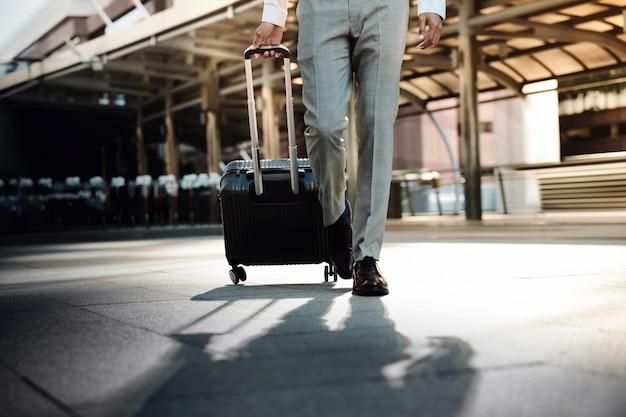 Seção baixa do jovem empresário andando no terminal de transporte moderno. entre na câmera. estilo de vida do viajante moderno.
