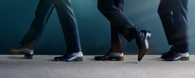Seção baixa do macho andando pela parede em movimento, homem de vestido preto formal