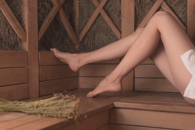 Seção baixa dos pés da mulher no banco de madeira na sauna