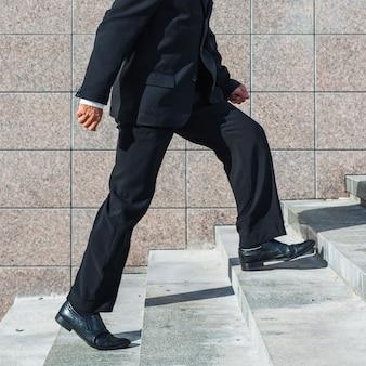 Seção baixa, vista, de, um, homem negócios, escalando escadaria