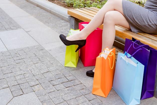 Seção baixa, vista, de, um, mulher, perna, com, multi coloriu, bolsas para compras